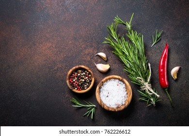 Selection of spices herbs and greens on dark rusty stone table. Ingredients for cooking. Food background. Top view copy space.
