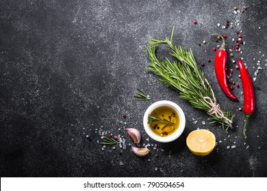 Selection of spices, herbs and olive oil on black stone table. Ingredients for cooking. Food background. Top view with copy space.