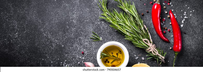 Selection of spices, herbs and olive oil on black stone table. Ingredients for cooking. Long banner format.