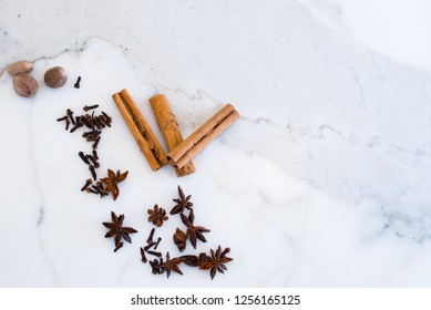 Selection of spices including cinnamon, cloves, star anise and nutmeg on marble countertop, overhead view