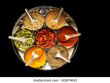Selection of spices with spoons arranged in a tin with black background
