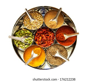 Selection of spices in tins with spoons, isolated on white