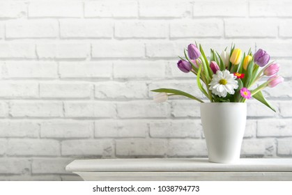 Selection of spring flowers inside a pot on top of a fireplace mantelpiece