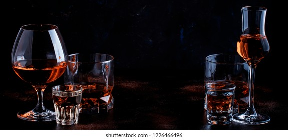 Selection of strong alcoholic drinks in glasses and shot glass in assortent: vodka, rum, cognac, tequila, brandy and whiskey. Dark vintage background, selective focus, copy space