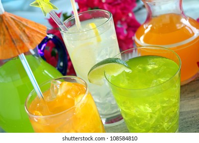 A selection of summer drinks with ice including lime, orange and lemon.