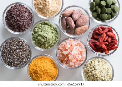 Selection of superfoods on a white background - goji berries, chlorella, young barley powder, dulse seaweed, maca, chia seeds, turmeric, himalayan sea salt, hemp seeds, raw cocoa nibs