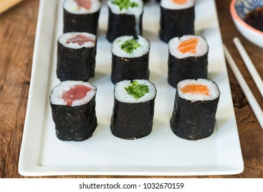 A selection of sushi rolls with salmon, tuna, cucumber and soy sauce dip.