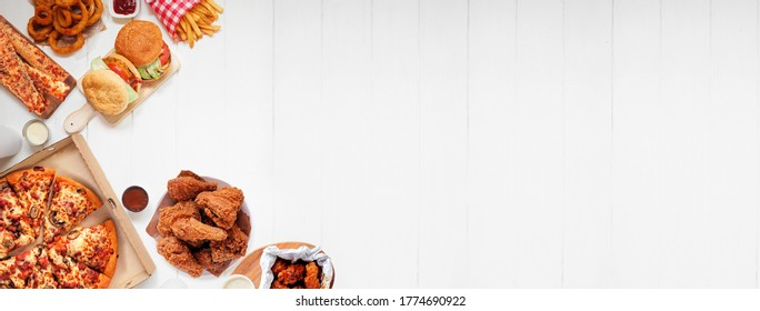 Auswahl von Schnellimbiss und Schnellspeisen. Banner an der Ecke. Pizza, Hamburger, gebratenes Huhn und Seitenwände.  Draufsicht auf weißem Holzhintergrund mit Kopienraum.