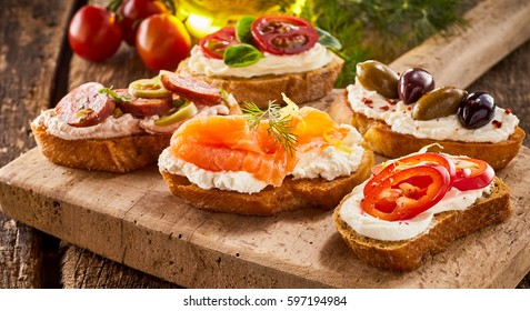 Selection of tasty bruschetta or canapes on taosted baguette and quark cheese topped with smoked salmon, olives, tomato and chorizo sausage