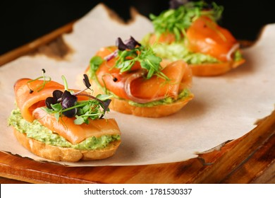 Selection of tasty bruschetta or canapes with salmon closeup. salmon tapas with guacamole and topped microgreen