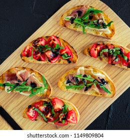 Selection of tasty Italian bruschetta or canapes on toasted baguette topped with tomatoes, Prosciutto di Parma, arugula and balsamic glasse sauce on cutting board on dark stone background. Top view.