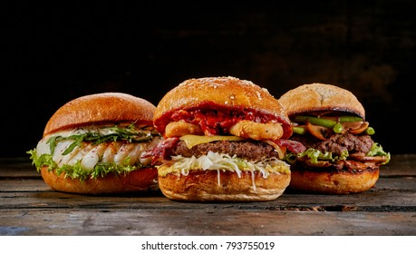 Selection of three different gourmet burgers with a fish seafood burger, surf and turf with bacon and squid and avocado and guacamole burger