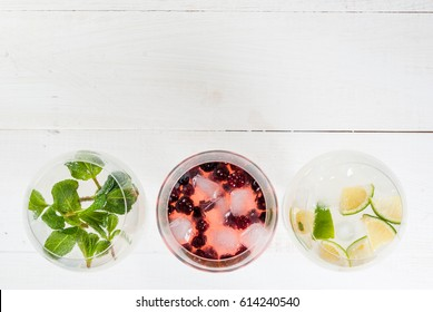 Selection of three kinds of gin tonic: with blackberries, with lime, with mint leaves. In glasses on a white background. Copy space top view