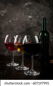 Selection of three kinds (Varieties) of wine - red, white and pink. In glasses, with an open bottle. On a dark concrete background. Copy space vertical
