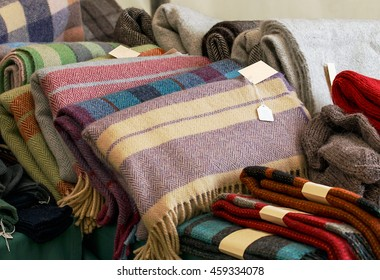 Selection of throws traditionally made of wool in a pile for sale at market traders, great example of crafting industry.