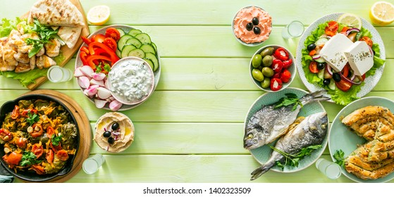 Selection of traditional greek food - salad, meze, pie, fish, tzatziki, dolma on wood background, top view