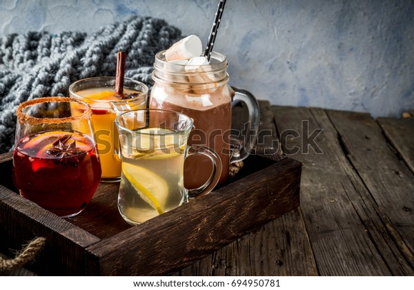 Selection of various autumn traditional drinks: hot chocolate with marshmallow, tea with lemon and ginger, white pumpkin spicy sangria, mulled wine. On wooden rustic table, copy space, selective focus