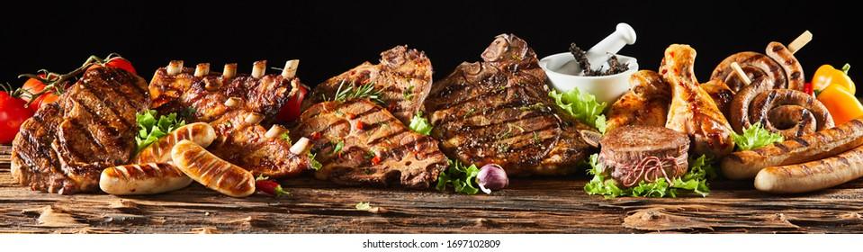Eine Auswahl an verschiedenen gegrillten Feinschmeckerfleisch auf rustikalem Holzbrett mit schwarzem Hintergrund.