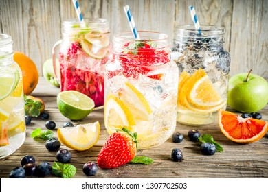 Selection various fruit and berry lemonade drinks, refreshment infused water, in mason jars, with fresh strawberry, lemon, lime, oranges, blueberry, wooden background copy space
