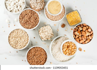 Selection various types cereal grains groats  in different bowl on white marble background, above