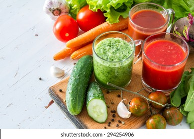 Selection of vegetable juices and ingredients, wood board, white wood background