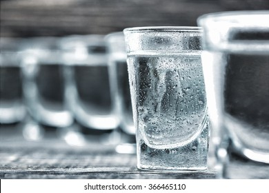 selectiv focus glasses of  cold vodka  on wooden table