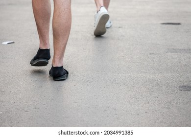 Selective blur on unrecognizable legs and feet of caucasian white male wearing flip flop slippers sandals with black socks. Flipflops and socks are a german stereotype considered as a faux pas.