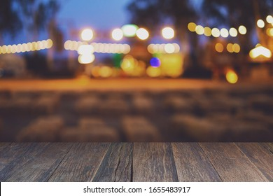 Selective Empty wooden table in front of abstract blurred festive light background.