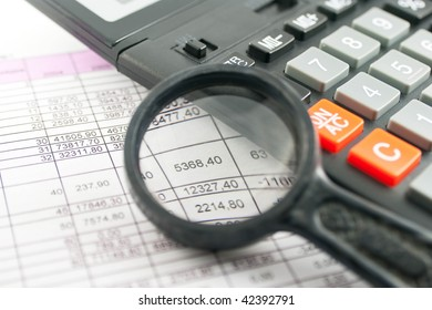 selective field shot looking through magnifying glass at US tax form on desk with calculator