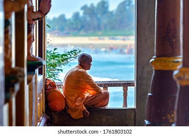 Selective focus. 12/28/2019 Gokarna. Karnataka. India. the monk of the Hindu temple Sri Rama Temple is sitting on a railing and watching the sunset in the ocean.