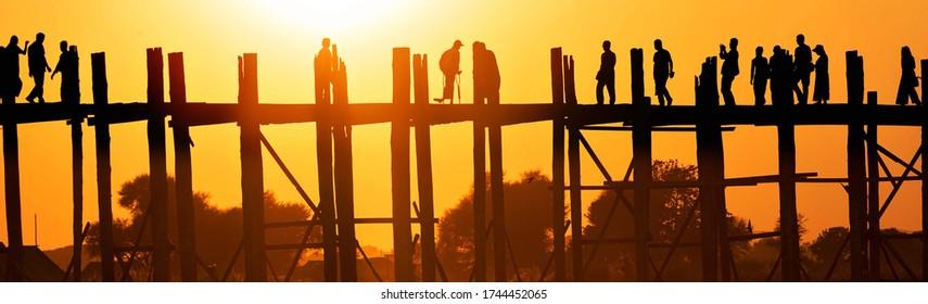 Selective focus. 19/02/2020 Mandalay, Myanmar (Burma), Sunset with silhouettes at U bein Bridge in Amarapura across Ayeyarwady Riverin. U-bein Bridge is oldest and longest teak wooden bridge