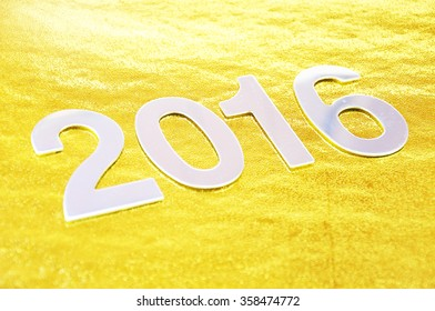 selective focus of 2016 number over golden background.