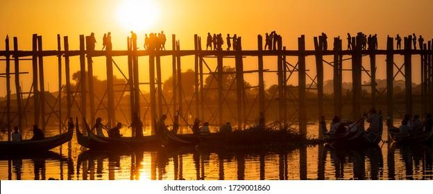 Selective focus, 25/01/2020 Mandalay, Myanmar (Burma), Sunset with silhouettes of  unrecognizable people U bein Bridge in Amarapura across Ayeyarwady Riverin. U-bein