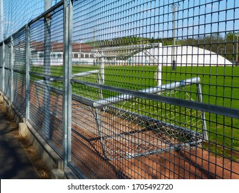 selective focus. Abandoned, empty soccer and sporst field. galvanized metal fence. goal turned on the side. out of use and service. lockdown of facility due to Covid-19 or Coronavirus concept.
