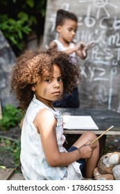 selective focus of african american child holding pencil while sitting near kid and chalkboard