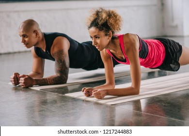 selective focus of african american couple of athletes doing plank on fitness mats at gym