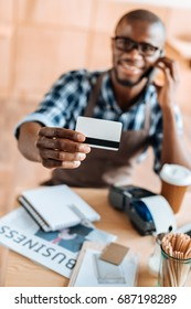 selective focus of african american man showing credit card in coffee shop