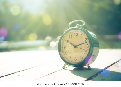 Selective focus of alarm clock with nature bokeh background.