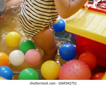 Selective focus of Asian baby girl legs standing in a bathtub with water of little depth - for young babies safety, do not put them in a water higher than their knees, to reduce a risk of drowning