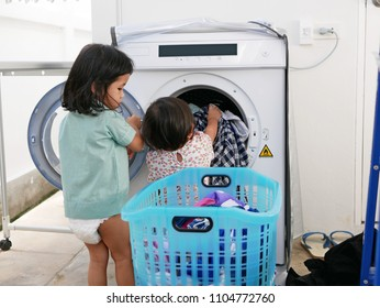 Selective focus of Asian baby girl, 15 years old, trying her best to load washed clothes into an electronic dryer with help from her older sister - baby's development through doing housework