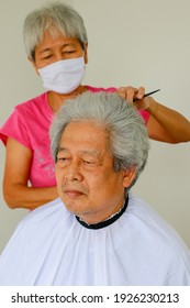 Selective focus. Asian Retirement hobby. Elderly husband lets his wife try her haircut at home. Because of COVID-19