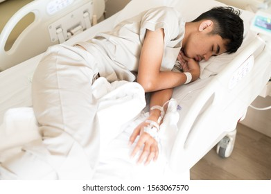 Selective focus Asian young boy sleeping on hospital bed during treatment and blurry set iv fluid intravenous drop saline.Young man is sick.Medical treatment concept.