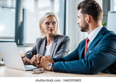 selective focus of attractive blonde woman in glasses looking at businessman near laptop