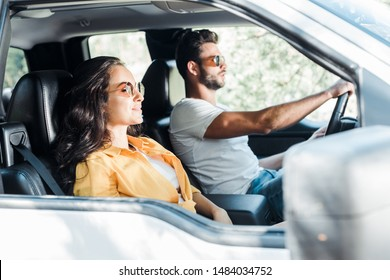selective focus of attractive girl near man driving car