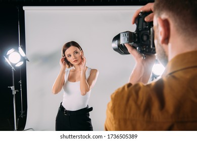Selective focus of attractive model posing at photographer with digital camera in photo studio