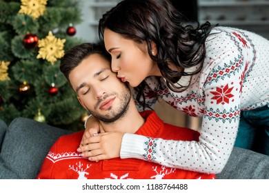 selective focus of attractive woman kissing sleeping boyfriend on sofa near christmas tree at home