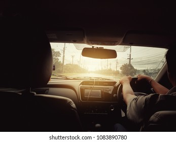 Selective focus of backside of a man driving a car on the road with sunlight