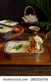 selective focus of baked cheese spaghetti in a alumunium foil on a wooden coaster against dark background