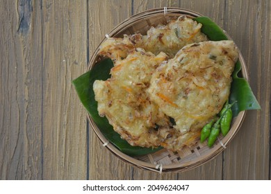 Selective focus of Bala-bala or Bakwan or Vegetable fritters, Indonesian traditional snacks made from flour batter with diced carrot and cabbage served on bamboo tray.