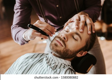 selective focus of barber shaving bearded man with closed eyes